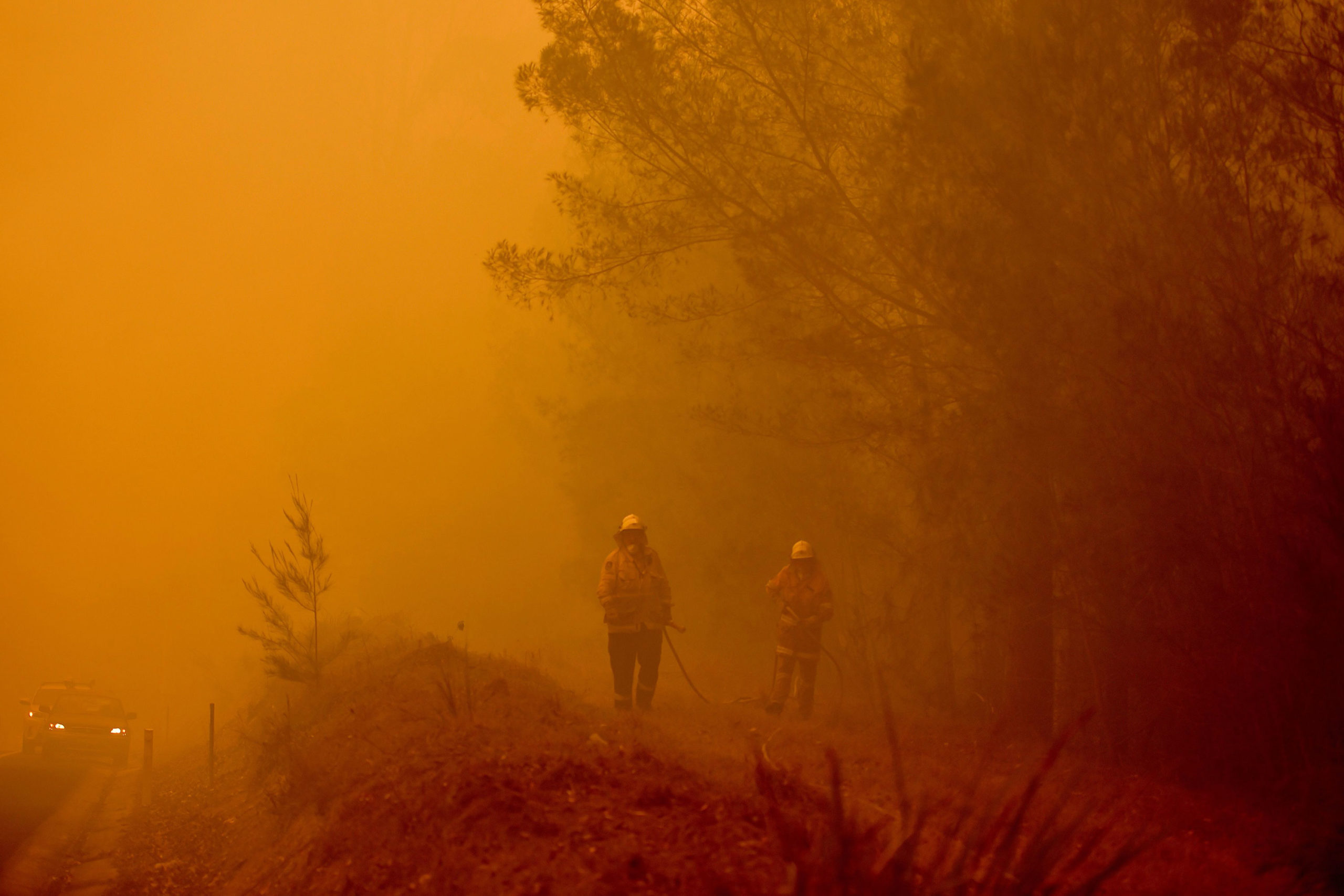 Firefighters tackle a bushfire in thick smoke in the town of Moruya, south of Batemans Bay, in New South Wales on Saturday.