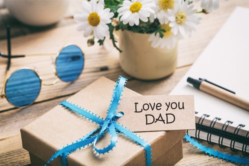Father's day. Gift box with love you dad tag, blur office desk background
