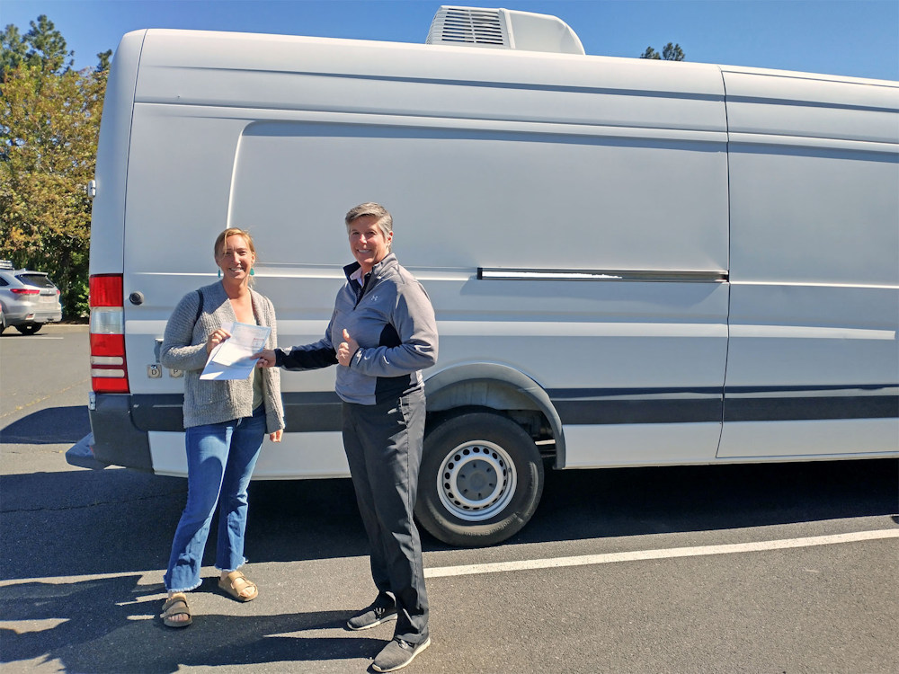 Johannah Johnson Weinberg, founder of the Companion Animal Medical Project (CAMP), receives papers for a van given by the Humane Society of Central Oregon Executive Director Sabrina Slusser