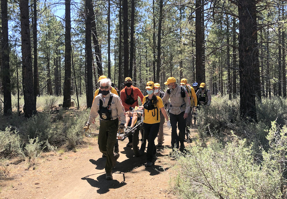 Deschutes County Sheriff's Search and Rescue volunteers bring wheeled litter, injured mountain bike rider to Phil's Trailhead parking lot on Friday