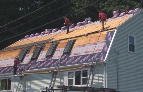 Workers put a new roof on Admira Depina's roof in Randolph.