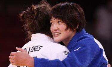 Japan's Chizuru Arai smiles while hugging Michaela Polleres of Austria after the Women's Judo 70kg Final