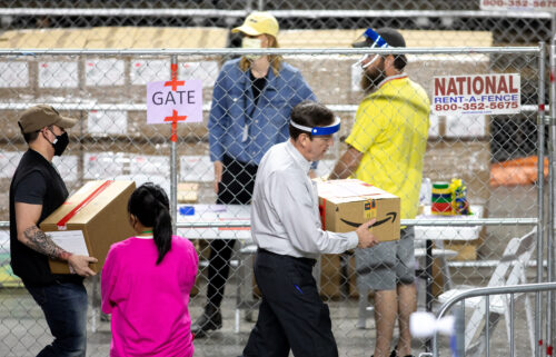 Former Arizona Secretary of State Ken Bennett (right) works to move ballots from the 2020 general election at Veterans Memorial Coliseum on May 1 in Phoenix