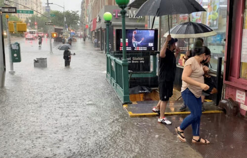 A person wades through floodwater as people exit the 157th St. metro station in New York City on July 8.