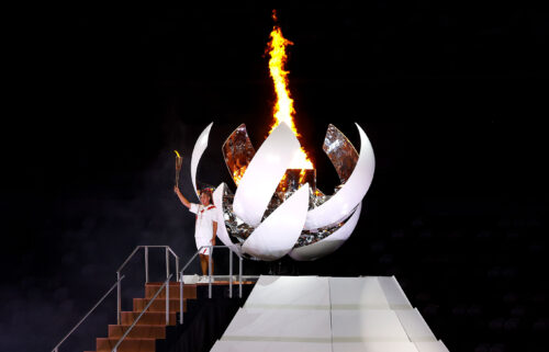 Naomi Osaka gestures after lighting the Olympic cauldron during the opening ceremony at the Olympic Stadium.