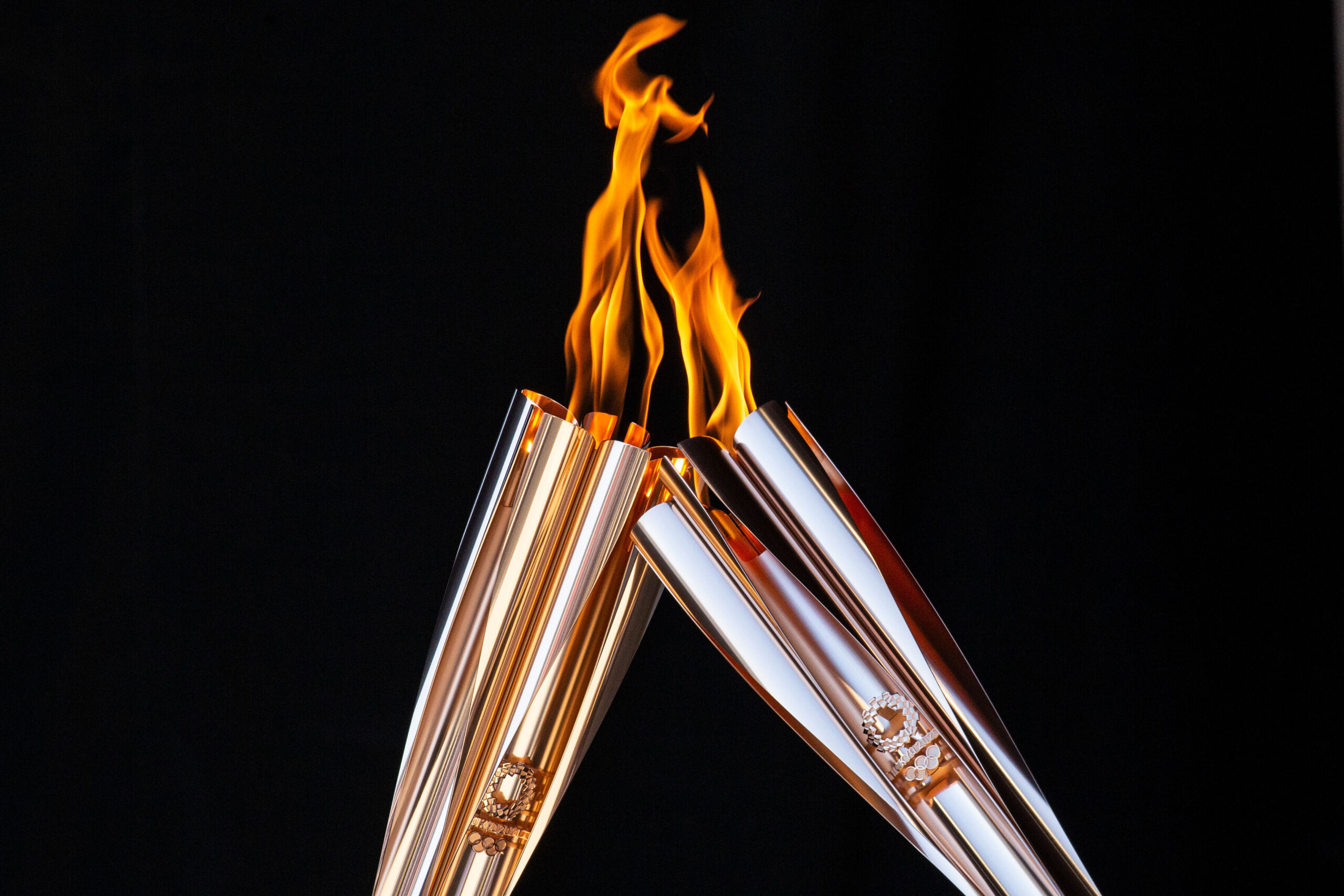 <i>Yuichi Yamazaki/Getty Images</i><br/>Torch bearers exchange the flame during the Olympic Torch Relay Celebration event on July 21