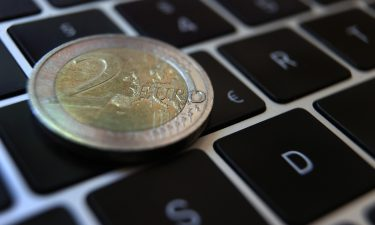 A two-euro coin lies on the keyboard of a laptop next to a euro sign. The European Central Bank is moving ahead with efforts to create a digital version of the euro as the use of cash declines and China ramps up tests of its own e-yuan.