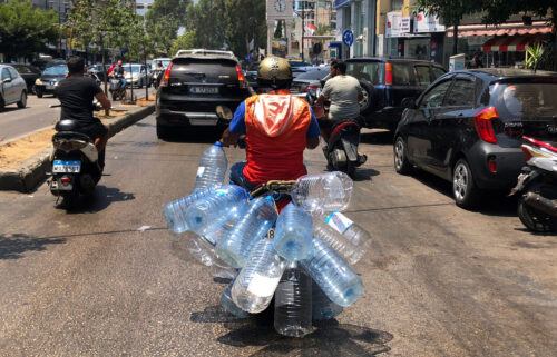 A man rides his scooter with empty water bottles to fill them with gasoline
