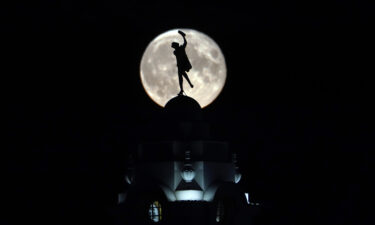 The full buck moon rises over a dancing lady on the Spanish City building in Whitley Bay