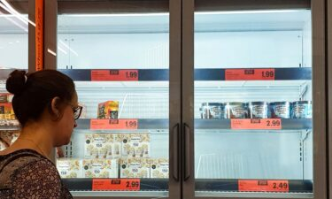 A customer looks at the depleted stock of ice cream at a Lidl supermarket. A dramatic surge in Covid-19 cases is forcing hundreds of thousands of workers to stay home in Britain