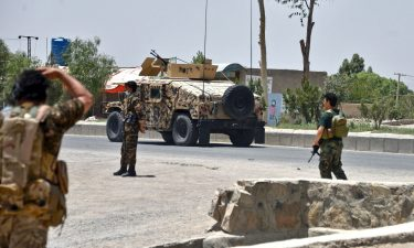 Afghan security personnel stand guard as Afghan security forces fight the Taliban in Kandahar on July 9.