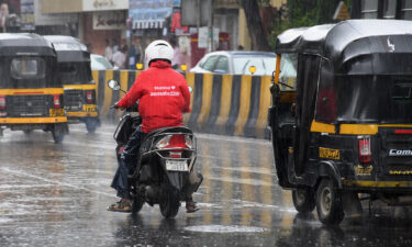 A Zomato delivery man is seen riding along the streets of Mumbai. Shares in Zomato gained about 80% on their first day of trading on Mumbai's stock exchange.