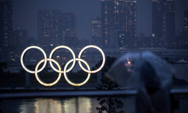 A woman walks past the Olympic Rings lit up at dusk in the rain