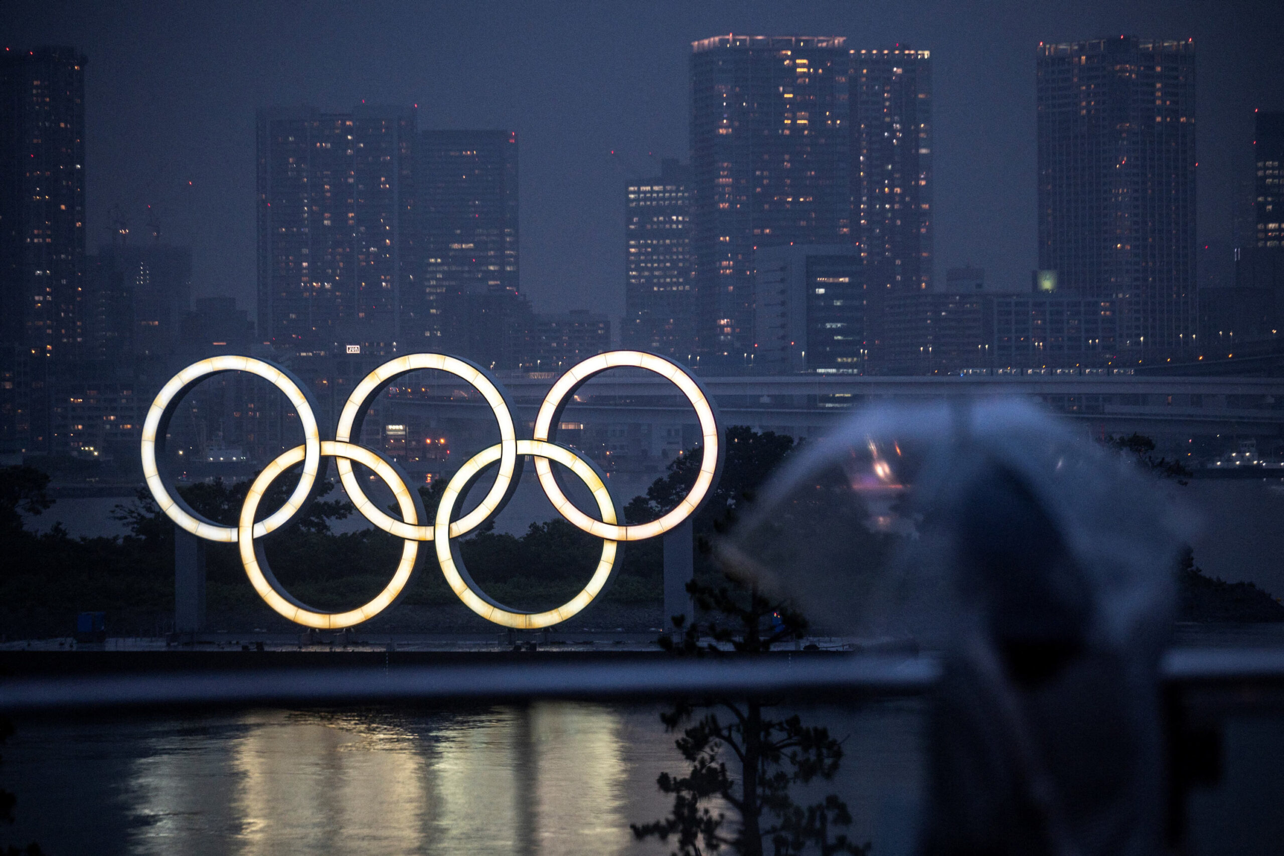 <i>CHARLY TRIBALLEAU/AFP/Getty Images</i><br/>A woman walks past the Olympic Rings lit up at dusk in the rain
