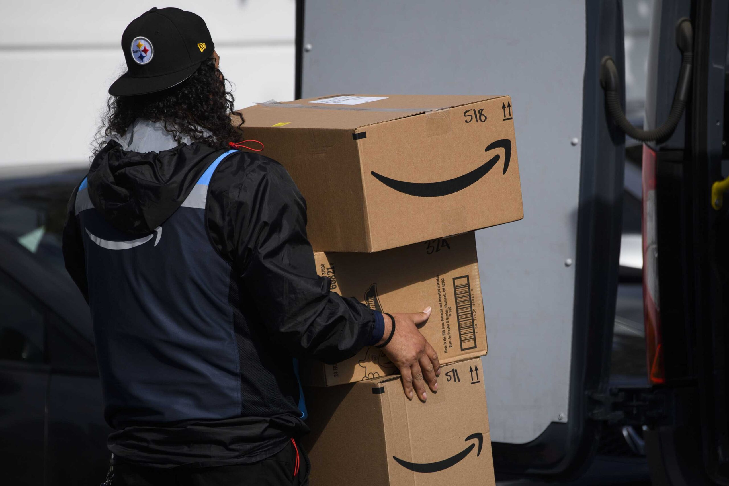 <i>PATRICK T. FALLON/AFP/Getty Images</i><br/>An Amazon.com Inc. delivery driver carries boxes into a van outside of a distribution facility on February 2 in Hawthorne