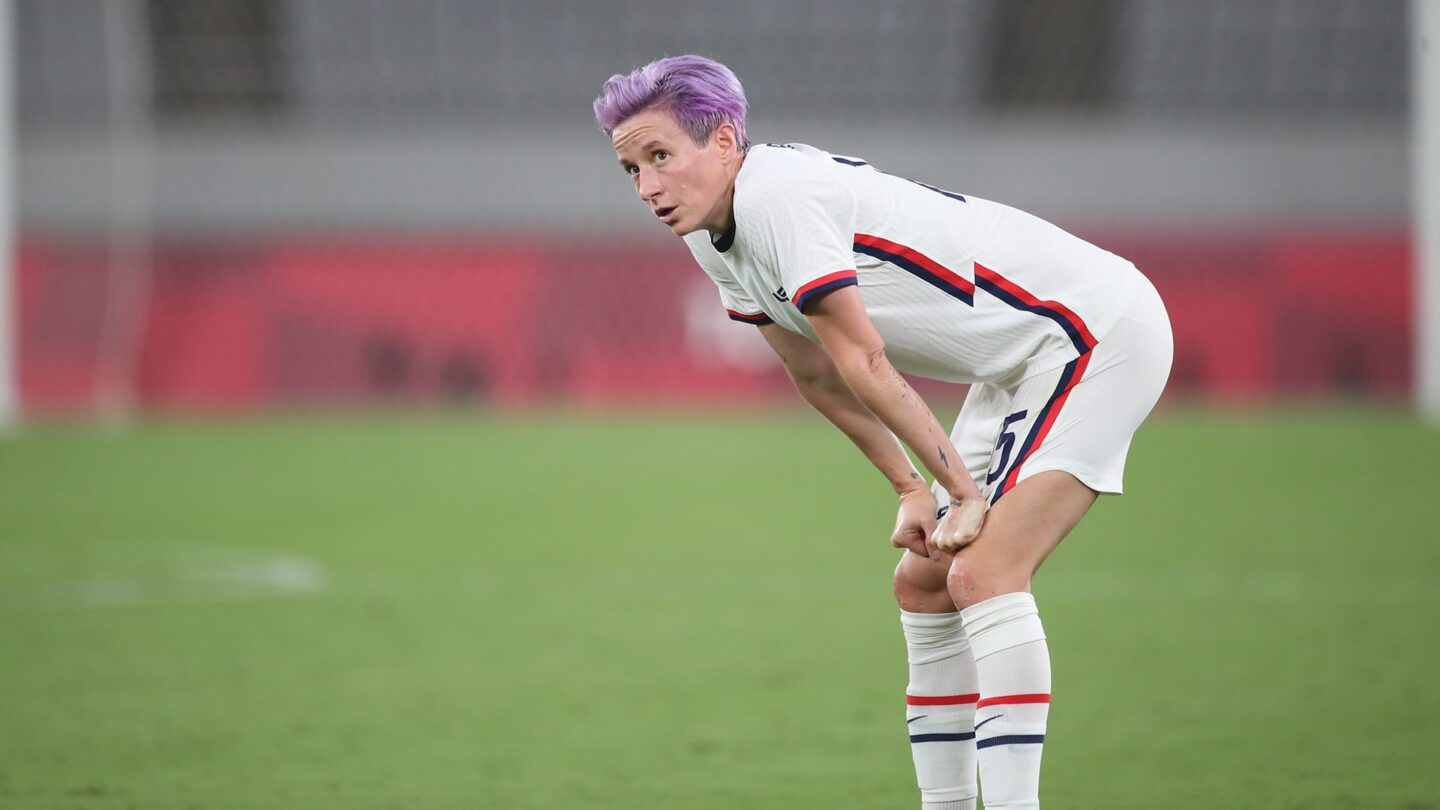 Megan Rapinoe puts her hands on her knees during a USWNT soccer match.