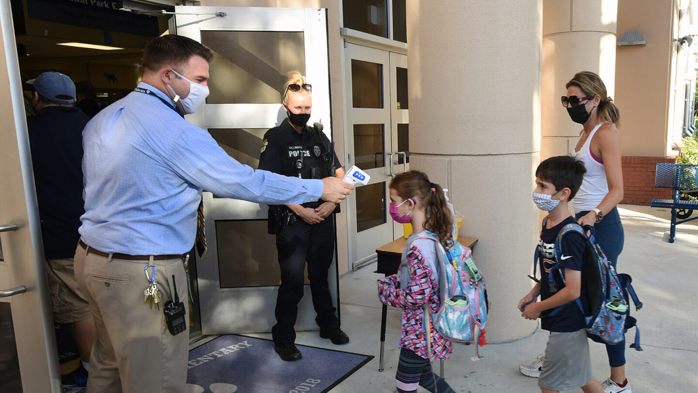 <i>Paul Hennessy/SOPA Images/Getty Images</i><br/>Judge John Cooper ruled Friday against Florida Gov. Ron DeSantis' ban on mask mandates in schools. Principal Nathan Hay checks students' temperatures as they arrive at Baldwin Park Elementary School in Orlando