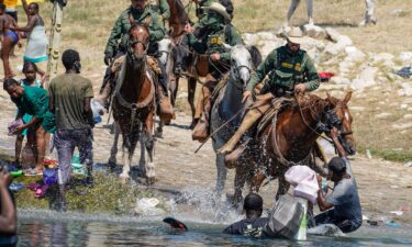 US Border Patrol agents on horseback try to stop Haitian migrants on Sunday from entering an encampment on the banks of the Rio Grande near the Acuna Del Rio International Bridge in Del Rio