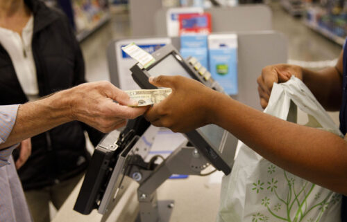 A customer hands cash to an employee while making a purchase at a Walmart location in Burbank