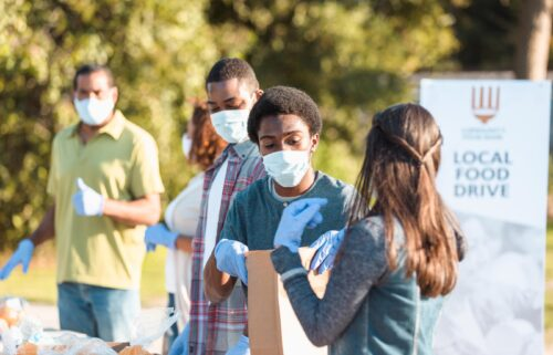 A young couple works together at the local food drive during COVID-19.  Everyone wears protective masks and gloves to slow the spread of disease.