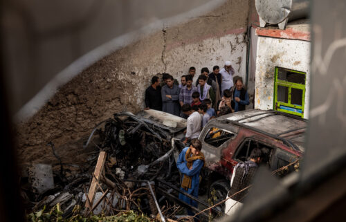 Relatives and neighbors inspect damage in the cramped courtyard of a house in Kabul