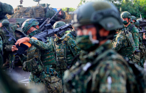 Taiwanese soldiers are seen holding grenade launchers and machine guns and driving tanks