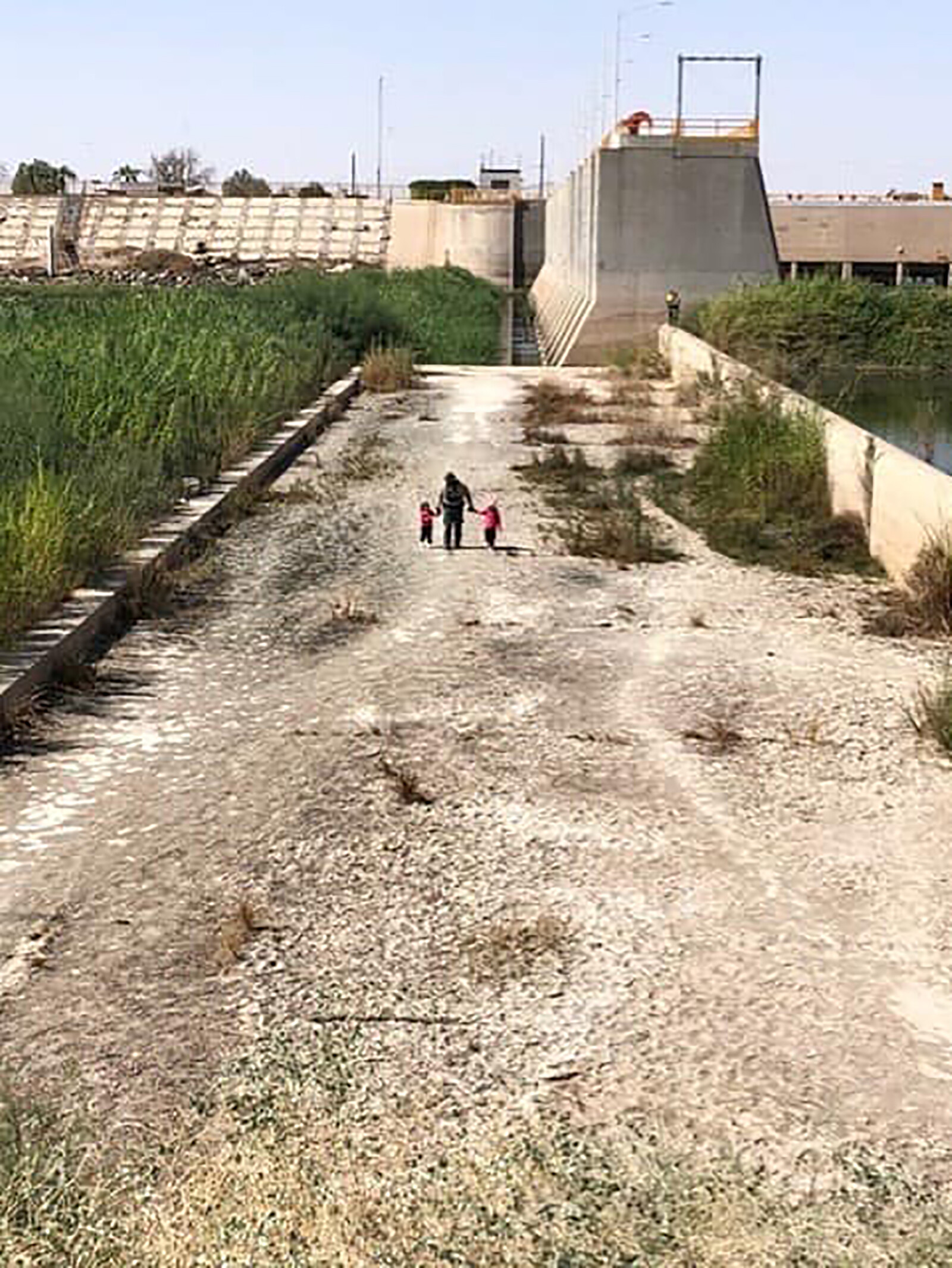 <i>US Border Patrol</i><br/>A US Border Patrol agent is seen walking with two young sisters found on October 12
