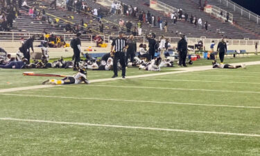 Players lie on the field as they take cover during a football game at Ladd-Peebles Stadium in Mobile